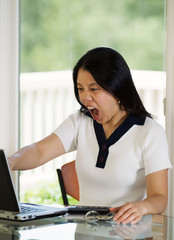 Mature woman expressing extreme anger while looking at her compu