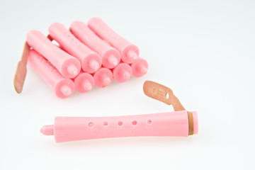 Close up pink plastic curler for hairstyle