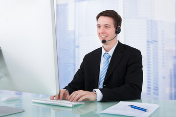 Confident Businessman Wearing Headset At Desk
