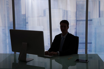 Businessman Working Overtime At Computer Desk