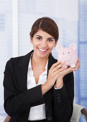 Happy Businesswoman Holding Piggybank In Office