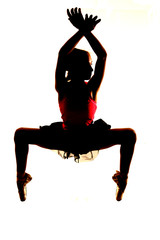 Silhouette of ballerina on her toes knees bent hands up