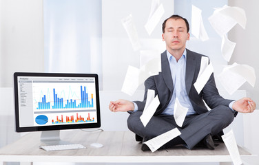 Businessman Meditating By Computer In Office
