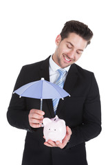 Businessman Sheltering Piggybank With Umbrella