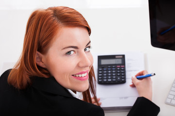 Businesswoman Using Calculator At Office Desk