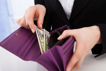 Businesswoman Putting American Banknotes In Wallet