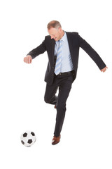 Businessman Kicking Soccer Ball