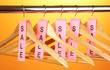 wooden clothes hangers as sale symbol on orange background.
