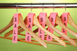 wooden clothes hangers as sale symbol on green background.