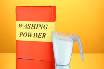 Box of washing powder with blue measuring cup,