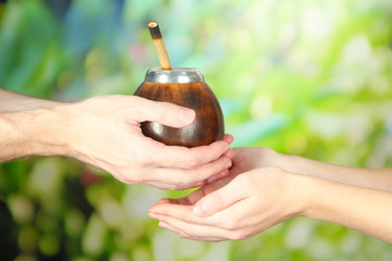 Man hands giving calabash and bombilla with yerba mate,