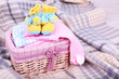 Baby clothes in basket on plaid in room
