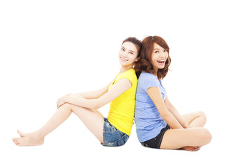 two young woman sitting and back to back