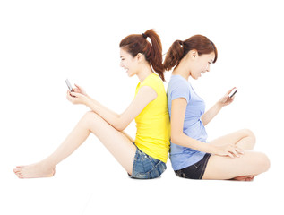 two happy young woman playing smart phone