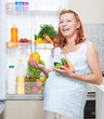 pregnant woman and refrigerator with health food vegetables