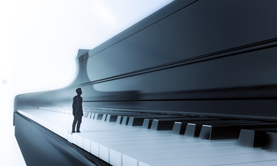 Tiny man standing on a piano
