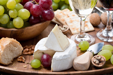 Camembert, fresh baguette, grapes and wine on wooden tray