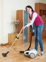 brunette woman cleaning with vacuum cleaner