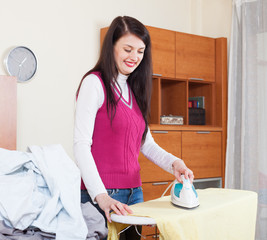 Smiling brunette woman ironing with iron