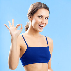 Cheerful woman in fitness wear, on blue