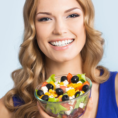 Woman with vegetarian salad, on blue