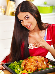 Woman cooking chicken at kitchen.