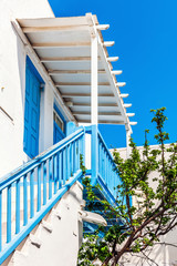 Traditional white house with blue railing and balcony in Mykonos