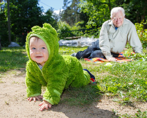 Child creeps away from grandfather outdoors
