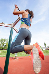 sport woman doing pull ups outdoors