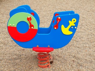 Children colorful wooden swinging bench in playground.