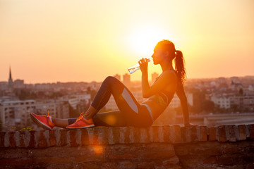 silhouette of a young sportive woman drinking water