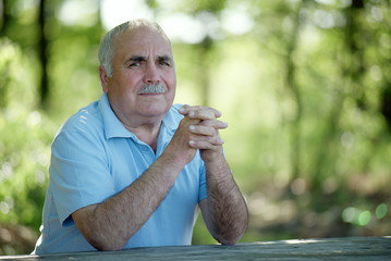 Elderly man sitting outdoors smiling at the camera