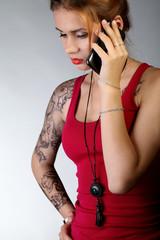 Молодая девушка с татуировкой говорит по телефону