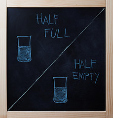 Half full and half empty concept drawn on blackboard