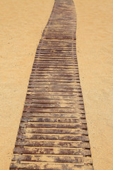 Wooden pathway on sandy beach