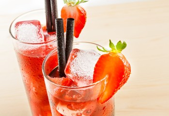 glasses of strawberry cocktail with ice on light wood table