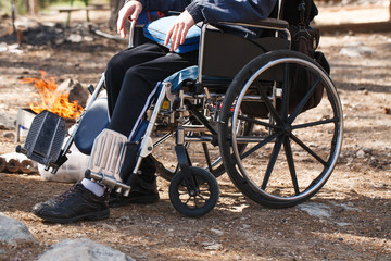 Man in a wheelchair in a park near the fire.