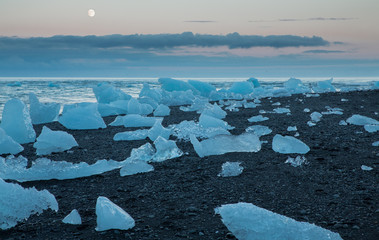 blue icebergs and sea with full moon