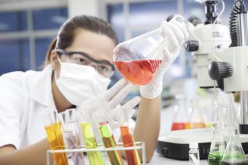 Chemist holding sample of red liquid in laboratory