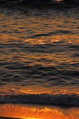 Golden sea waves and sand at sunset, closeup