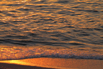 Golden sea waves and sand at sunset, closeup