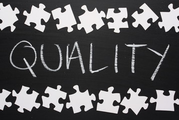 The word Quality on a blackboard with jigsaw pieces