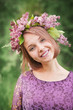 Beautiful cute girl in a wreath of lilacs