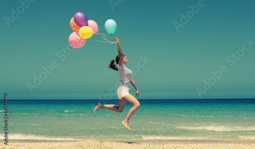 Leinwandbild Motiv beautiful woman with colorful balloons outside