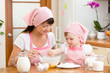 Mother and daughter preparing cookies together at kitchen