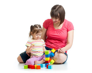 child girl and her mom play with building blocks