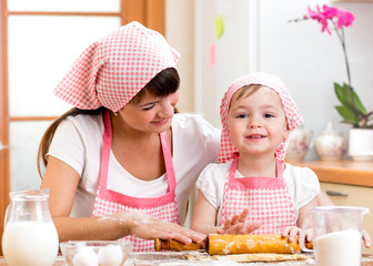 kid girl with her mother cook and roll out the dough