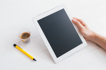 Hands of a man holding blank tablet device over wooden table