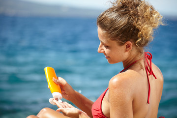 Woman applying sunscreen solar cream.