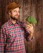 Happy farmer holding broccoli on rustic wood